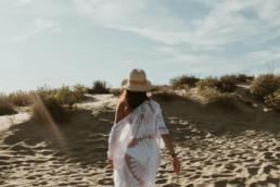 femme qui marche dans le sable et le dunes à la grande motte. Avec un paréo blanc et un chapeau de paille