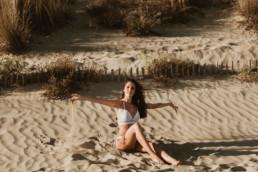 femme en maillot blanc assise sur le sable d'une plage à la grande motte, qui joue avec le sable entre ses doigts en fin de journée