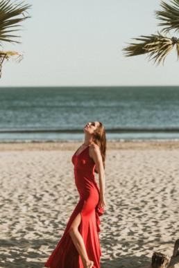 femme en robe de soirée longue rouge sur la plage entre deux palmier à la grande motte dans l'Hérault