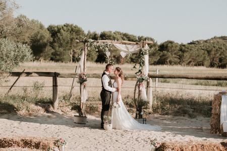 cérémonie laïque dans un cirque de chevaux. arche de cérémonie en tronc de bois, voile et rose rose. mariage champêtre